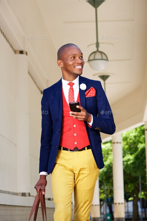 happy young african businessman walking outdoors with mobile phone - Stock Photo - Images