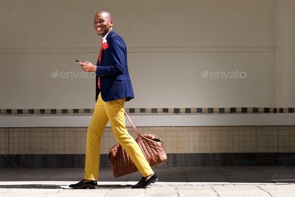 smiling african businessman walking with bag and phone - Stock Photo - Images