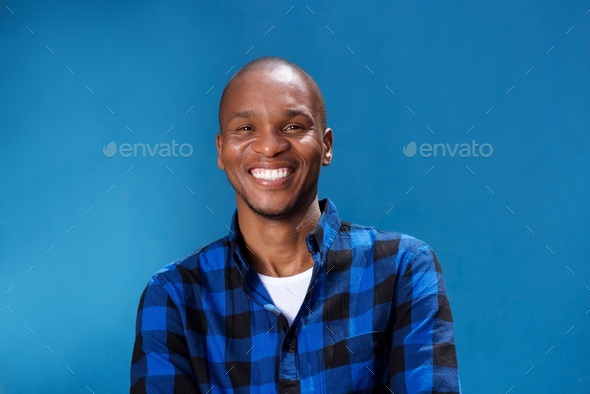 smiling young african man smiling against blue wall - Stock Photo - Images