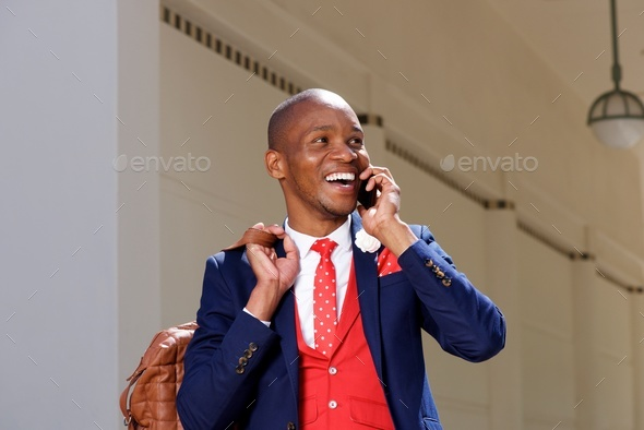 cheerful young african man in suit talking on mobile phone - Stock Photo - Images
