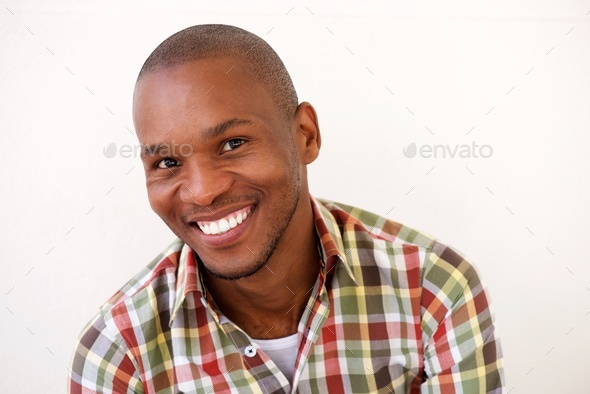 cheerful young black man smiling against white background - Stock Photo - Images