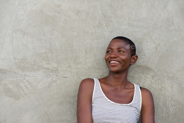 laughing beautiful black woman leaning against wall - Stock Photo - Images