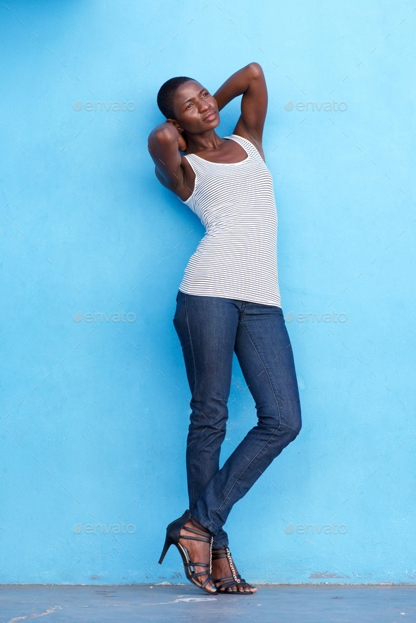 black woman leaning against blue wall with hands behind head - Stock Photo - Images