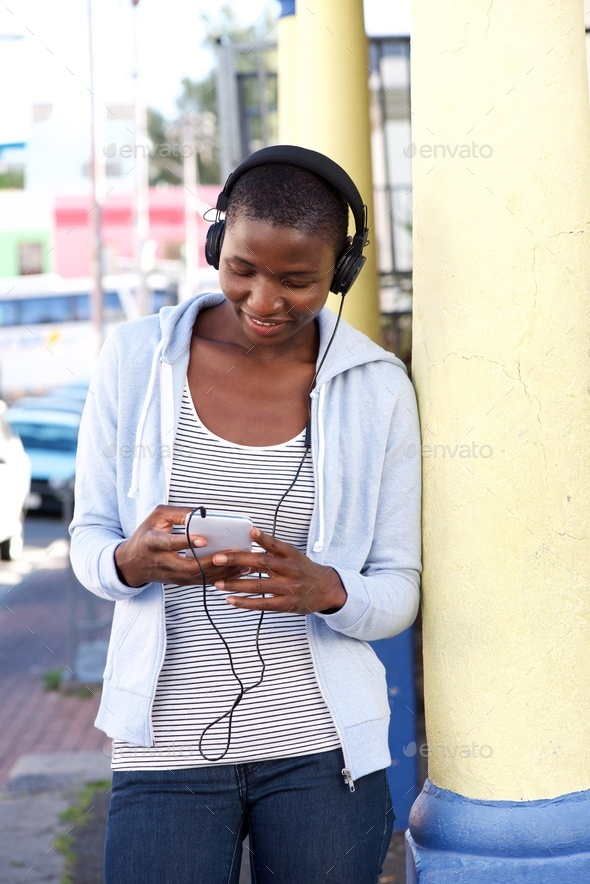 Woman outside leaning on column with phone and headphones - Stock Photo - Images