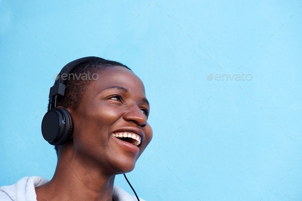 smiling african woman listening to music with headphones - Stock Photo - Images