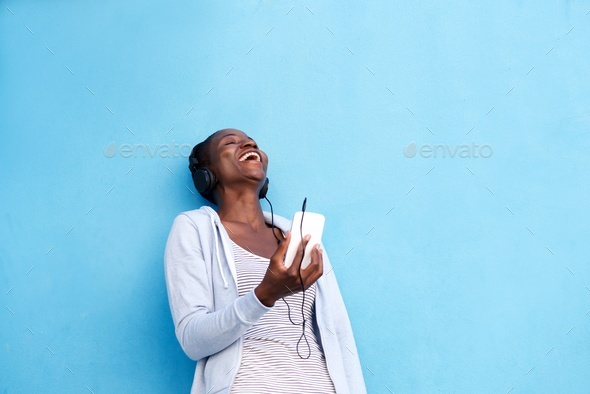 happy woman with smart phone and headphones by blue wall - Stock Photo - Images