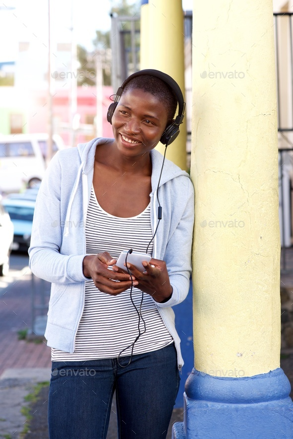 Portrait of happy woman outside listening to music - Stock Photo - Images