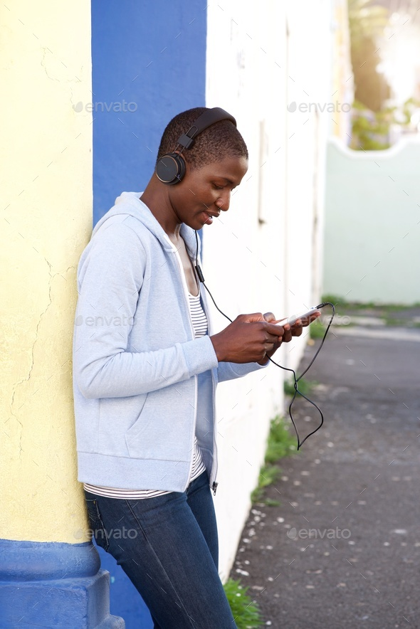 african woman listening to music outside with headphones - Stock Photo - Images