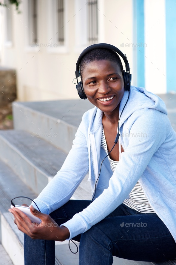 happy woman sitting on steps outside listening to music - Stock Photo - Images