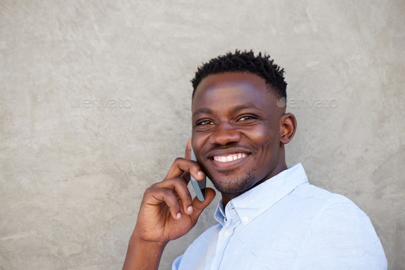 handsome young black man making a phone call by wall - Stock Photo - Images