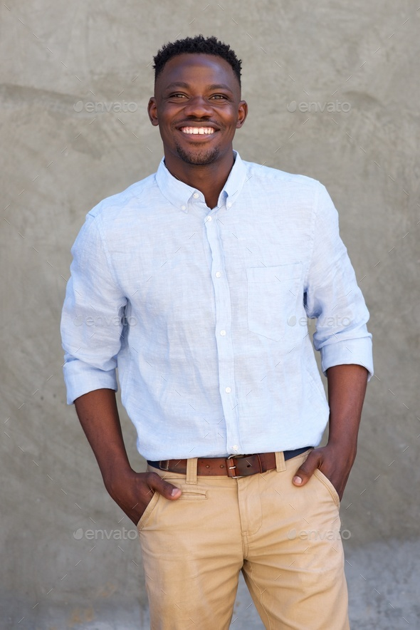 handsome african american man smiling by wall - Stock Photo - Images