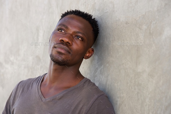 thoughtful young african man leaning against wall - Stock Photo - Images