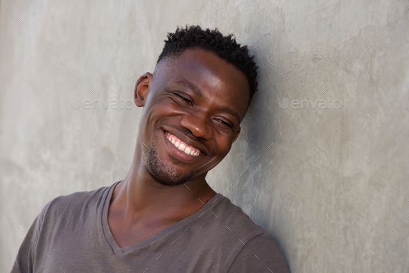 happy young african man leaning against wall - Stock Photo - Images