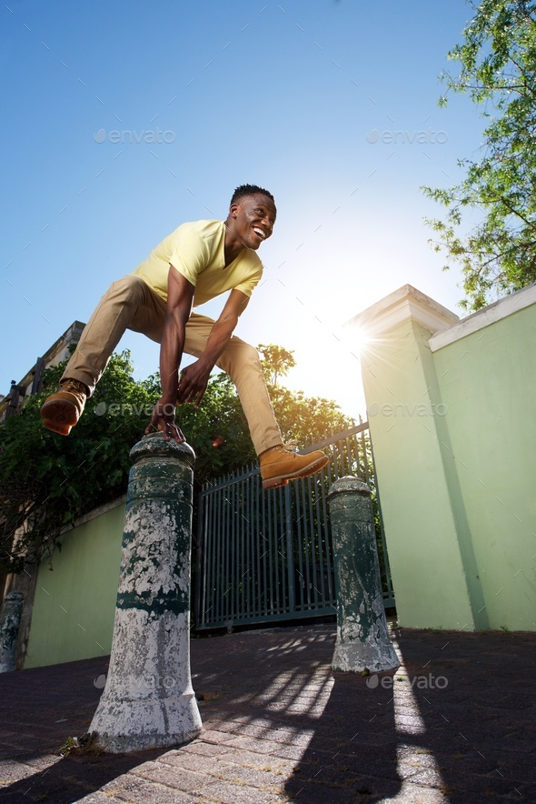 happy young african man jumping over iron post on sidewalk - Stock Photo - Images