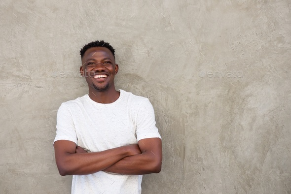 handsome young african man smiling with arms crossed by wall - Stock Photo - Images
