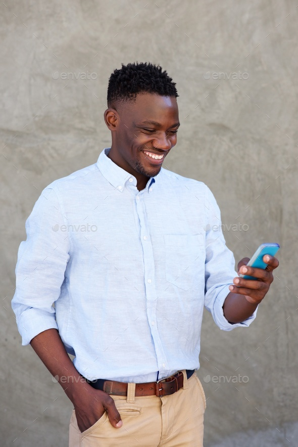 modern young black man reading text message on his mobile phone - Stock Photo - Images