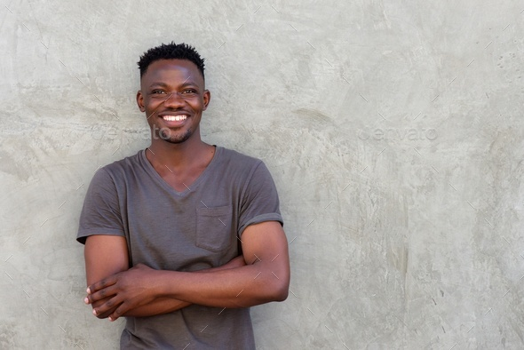 happy african man smiling with arms crossed by wall - Stock Photo - Images