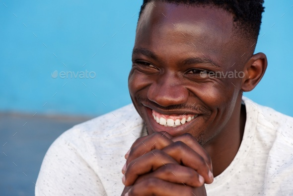 young african man smiling with hands in chin - Stock Photo - Images