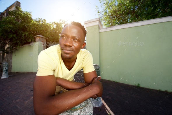 handsome young african man leaning over iron post on sidewalk - Stock Photo - Images