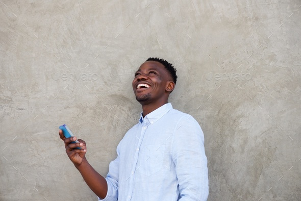cheerful young african man with mobile phone standing by wall - Stock Photo - Images