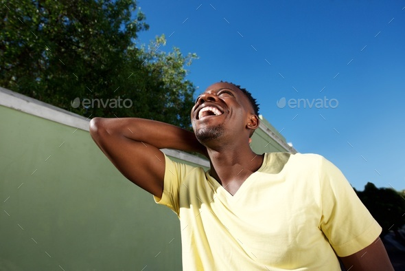 laughing young african man walking outside - Stock Photo - Images