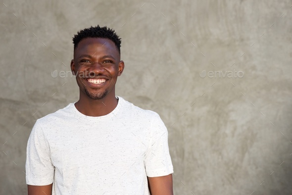 cheerful african man smiling by wall with copy space - Stock Photo - Images