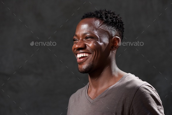 young african american man laughing and looking away - Stock Photo - Images