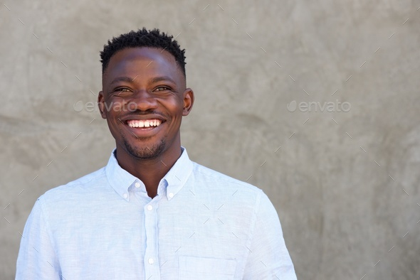 cheerful african american man standing against a wall - Stock Photo - Images