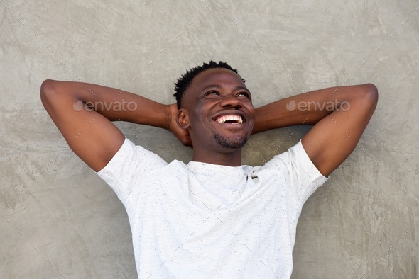 young african american man smiling with hands behind head - Stock Photo - Images