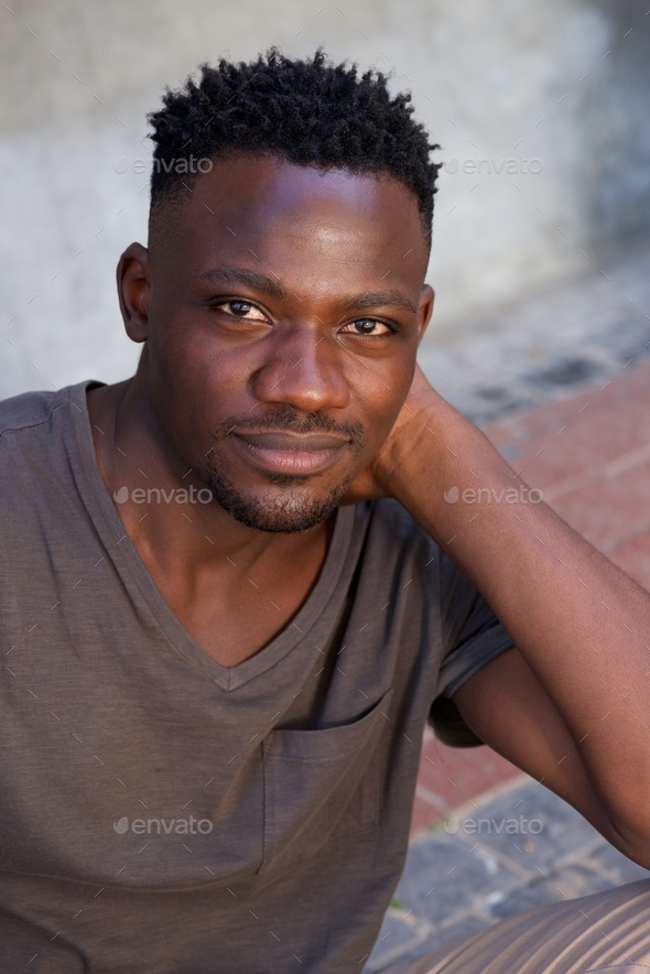 handsome young african man sitting outside - Stock Photo - Images