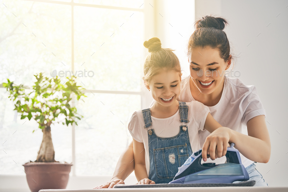 mother and daughter ironing at home - Stock Photo - Images