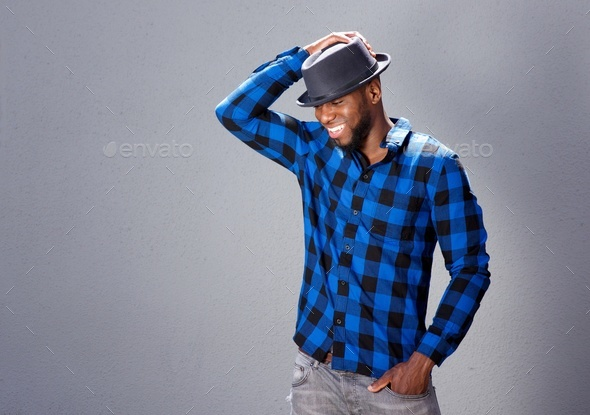 happy handsome man laughing with hand to hat - Stock Photo - Images
