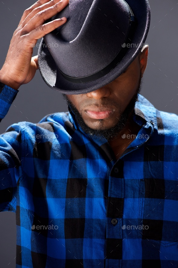 handsome man with hand to hat looking down - Stock Photo - Images