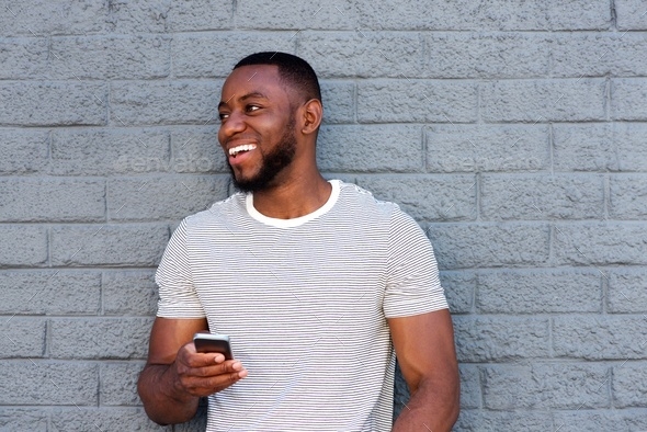 smiling man with cell phone leaning on gray wall - Stock Photo - Images