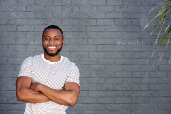 smiling handsome man standing with arms crossed - Stock Photo - Images
