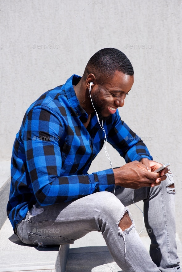 handsome man smiling with headphones and smart phone - Stock Photo - Images
