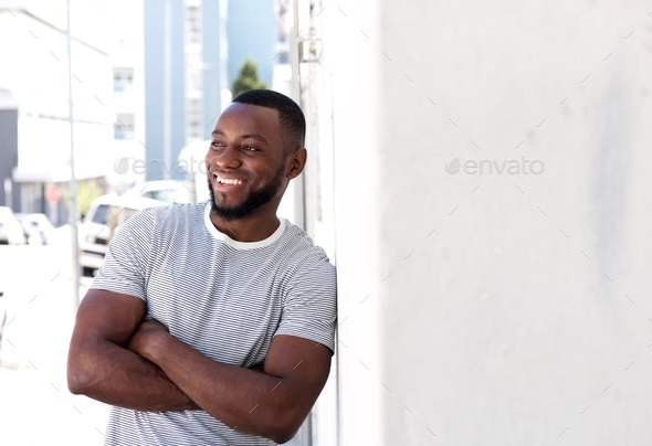 smiling man leaning on wall outside in city - Stock Photo - Images