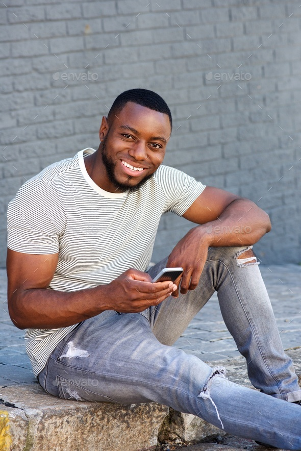 smiling man with smart phone sitting on curb outside - Stock Photo - Images