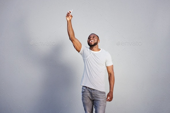 laughing man standing with smart phone in raised hand - Stock Photo - Images