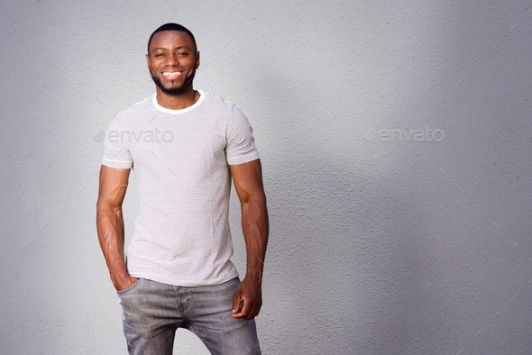 muscular man smiling and standing against gray background - Stock Photo - Images