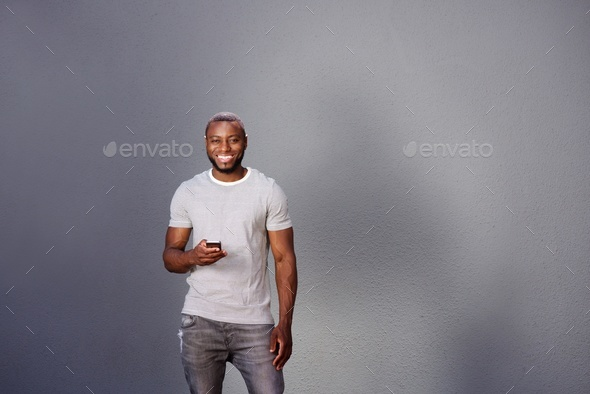 handsome man with smart phone standing by gray wall - Stock Photo - Images