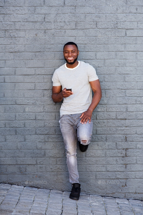 smiling man with smart phone leaning on gray wall - Stock Photo - Images