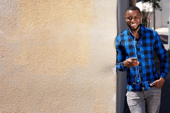 smiling man leaning against wall with smart phone and earphones - Stock Photo - Images