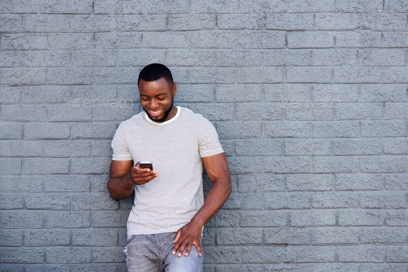 smiling man with mobile phone leaning on brick wall - Stock Photo - Images