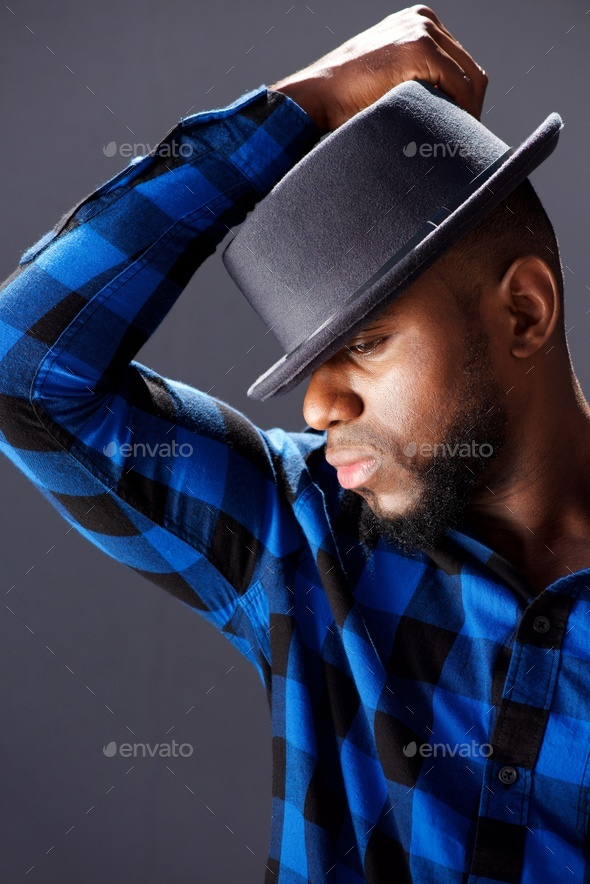 side portrait of trendy handsome man with hat - Stock Photo - Images