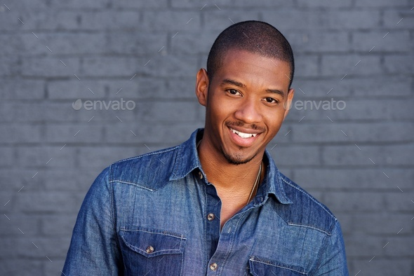 cool black guy smiling with blue shirt - Stock Photo - Images