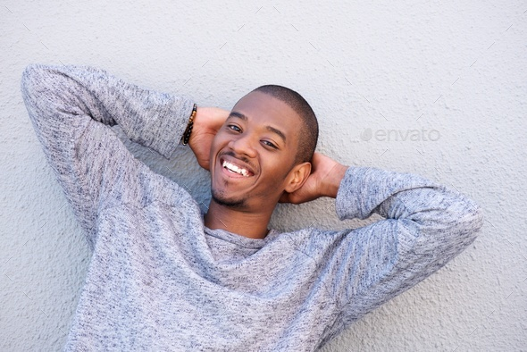 happy young black guy smiling with hands behind head - Stock Photo - Images