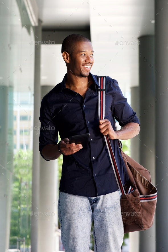 happy young black man walking with tablet and bag - Stock Photo - Images
