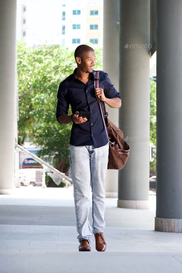 cool black guy walking in the city with mobile phone and bag - Stock Photo - Images
