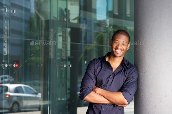 confident young black man smiling with arms crossed - Stock Photo - Images